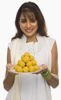 Woman with plate of ladoos